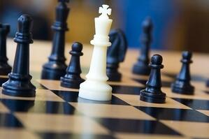White king and black opponents on chessboard.jpeg